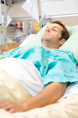 icu: Male patient resting on bed in hospital Stock Photo