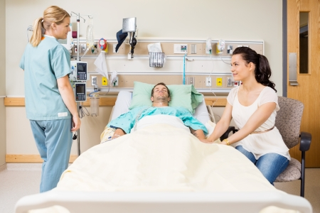 care giver: Young woman holding patients hand while looking at nurse in hospital room
