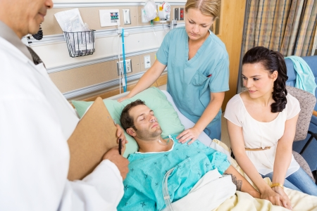 Loving woman holding patients hand while doctor and nurse examining him in hospital photo