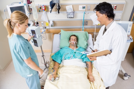 High angle view of doctor and nurse examining critical patient in hospital photo