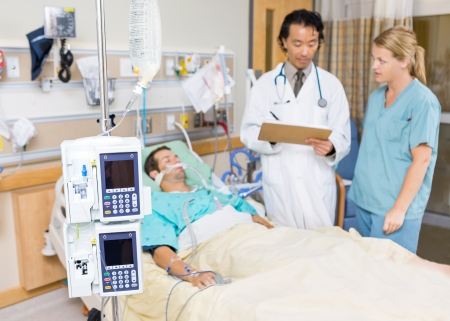 infusion: Dialysis machine with patient and doctor in background at hospital