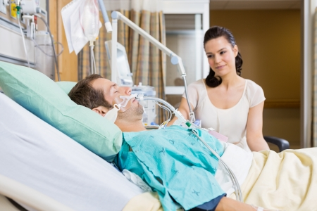 intubation: Beautiful woman looking at man lying on bed in hospital Stock Photo