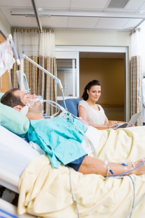 Portrait of young woman with laptop sitting by patient in hospital room photo