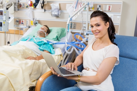 intubation: Portrait of beautiful woman with laptop sitting by male patient in hospital room