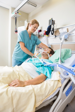 nurse and patient: Friendly nurse adjusting patients pillow in hospital Stock Photo
