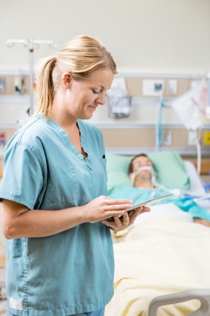 icu: Mid adult nurse using digital tablet while patient resting in background at hospital
