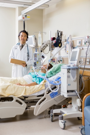 icu: Portrait of male doctor with patients report standing by bed in hospital room Stock Photo