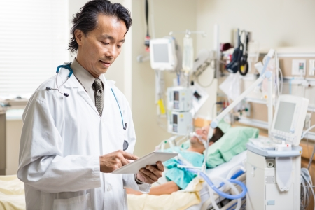 icu: Mid adult doctor examining patients report on digital tablet in hospital room Stock Photo
