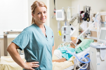 Portrait of confident nurse standing with hand on hip while patient resting in background at hospital
