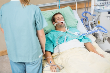 intensive care unit: High angle view male patient sleeping with nurse standing by in hospital