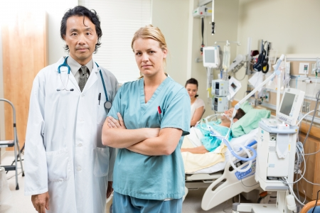 icu: Portrait of confident doctor and nurse with patient resting in background at hospital