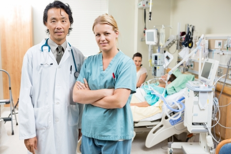 Portrait of confident nurse and doctor with patient resting in background at hospital photo