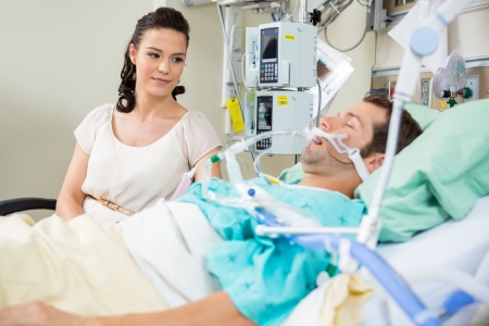 healthcare visitor: Beautiful woman looking at patient resting on bed in hospital