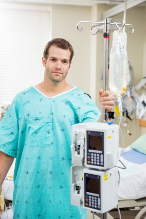 Portrait of young patient holding pole with drip bag and machine in hospital room photo