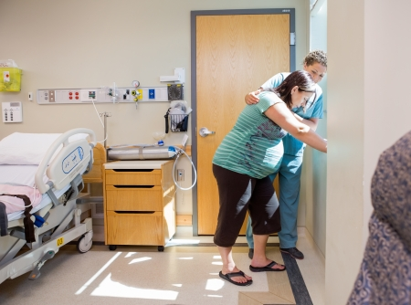 tensed: Mid adult female nurse comforting tensed pregnant woman leaning on window sill in hospital room