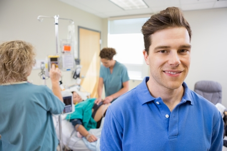 Portrait of happy mid adult man with nurses tending to birthing woman in background photo
