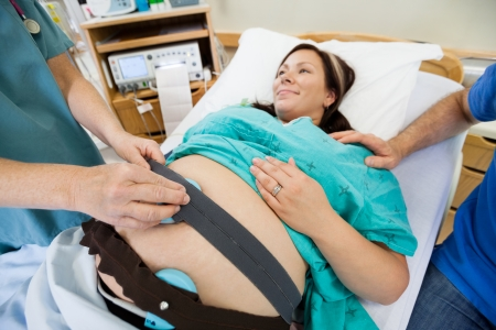 Midsection of nurse preparing pregnant woman for fetal heartbeat examination in hospital photo