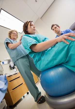 back exercise: Low angle view mature nurse assisting pregnant woman sitting on exercise ball while man looking at her in hospital