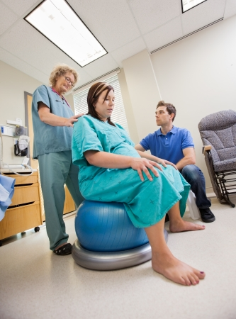 Mature female nurse assisting pregnant woman sitting on Pilate ball while man looking at her in hospital photo