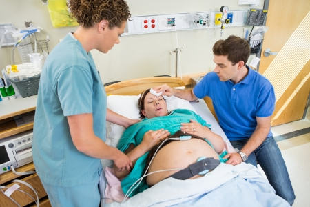 Loving mid adult man wiping forhead of pregnant woman's forehead in hospital Stock Photo - 23725181