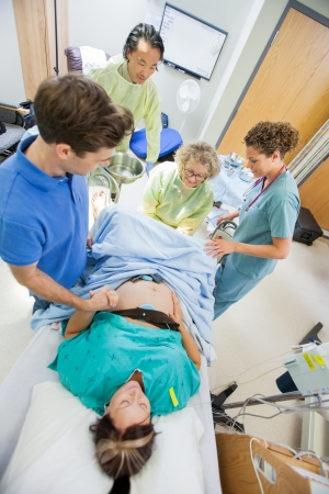 delivery room: High angle view of caring mid adult man holding womans hand during delivery in hospital room Stock Photo