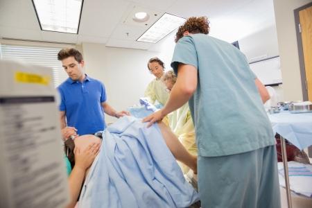 sala parto: Donna che partorisce in ospedale con il team medico e marito in luogo