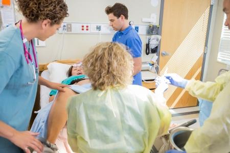 sala parto: Squadra Mecial consegna bambino in ospedale con il marito moglie confortante Archivio Fotografico