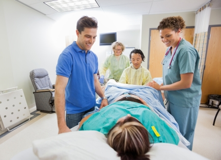 delivery room: Happy medical team and husband looking at pregnant woman during delivery in operating room