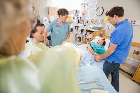 sala parto: Multi gruppo di medici etnica trasporta bambino, mentre il marito conforta moglie nella stanza d'ospedale Archivio Fotografico