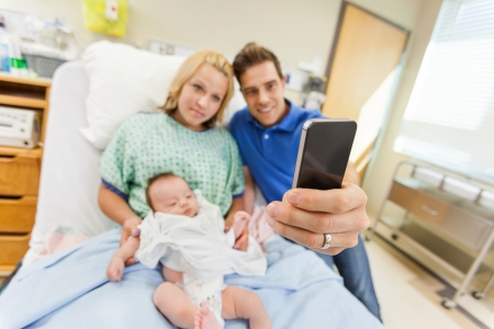 smart girl: Man with woman and newborn babygirl taking selfportrait through cell phone in hospital room