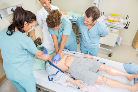 의사가 병실에서 대기하는 동안 더미 환자에서 CRP를 수행하는 간호사의 높은 각도보기 스톡 콘텐츠