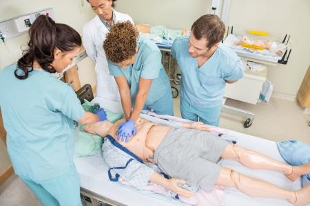 Visualizza alto angolo di infermieri che effettuano CRP sul paziente manichino mentre medico in piedi da nella stanza d'ospedale Archivio Fotografico - 23743702