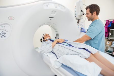 diagnostics: Male nurse preparing young patient for CT scan test in hospital room Stock Photo