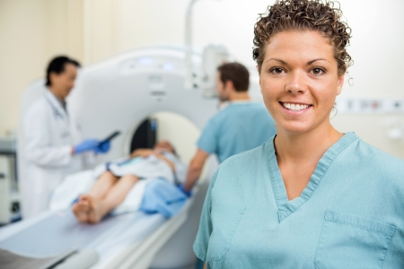 medical scanner: Portrait of happy female nurse with colleague and doctor preparing patient for CT scan in hospital