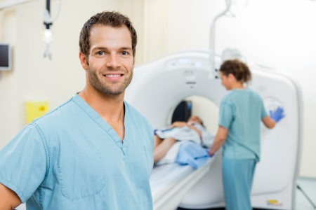 Portrait of male nurse with colleague preparing patient for CT scan in examination room Stock Photo
