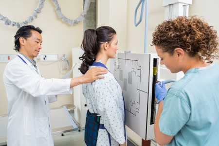 imaging: Doctor and nurse preparing young patient for chest xray in examination room Stock Photo