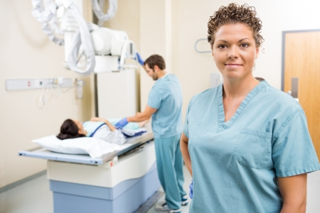 Portrait of female nurse with colleague preparing patient for xray in examination room photo