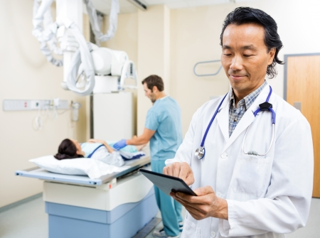 x ray equipment: Male radiologist using digital tablet while nurse preparing patient for xray in examination room Stock Photo