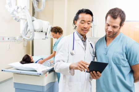 Male doctor and nurse using digital tablet while colleague preparing patient for xray in examination room Stock Photo - 23743731