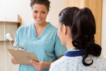 health facility: Happy mid adult nurse with clipboard looking at patient in ultrasound room