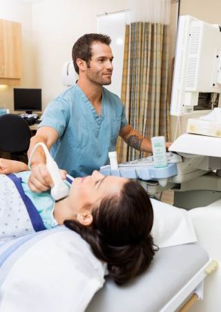 sonography: Young female patient undergoing thyroid gland test in hospital room