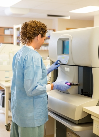 research facilities: Side view of female medical lab tech loading samples in hematology analyzer