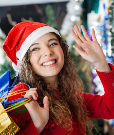 Happy young woman in Santa hat waving while carrying shopping bags at Christmas store photo