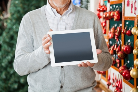 Midsection of senior man holding digital tablet at Christmas store photo