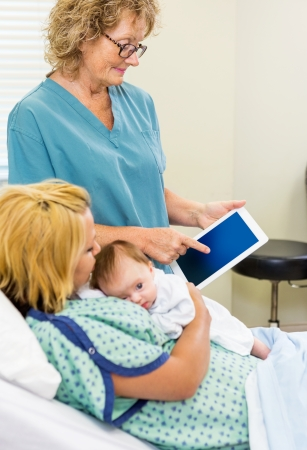 Mature nurse explaining reports on digital tablet to woman with newborn babygirl in hospital photo