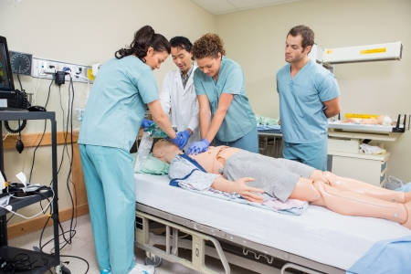 Female nurse performing CRP on dummy patient while doctor and colleagues looking at it in hospital room photo