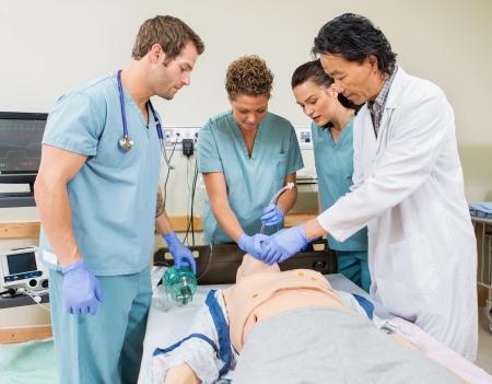 병원 방에 더미 환자의 입에 endotracheal 튜브를 삽입하는 간호사 지시 남성 의사