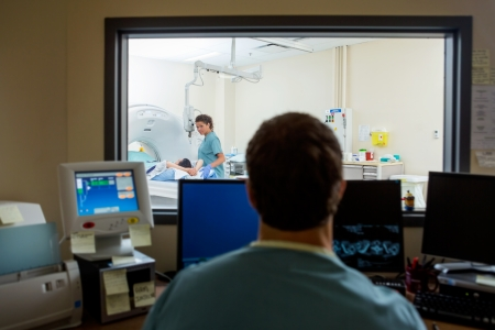 ct: Radiologist operating computers in CT scan lab
