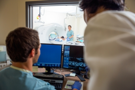 medical scanner: Medical team operating computers in CT scan lab