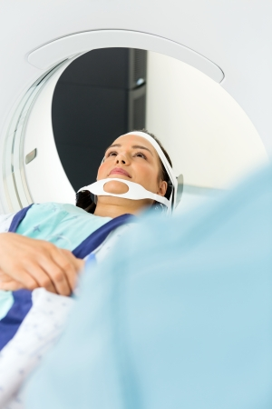 Young female patient undergoing CT scan in examination room photo